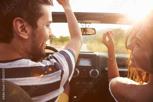 canvas print picture Young Couple Driving Along Country Road In Open Top Car