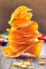Paprika chips with chili peppers on a wooden background