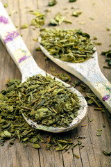 Dry green tea on a wooden spoon