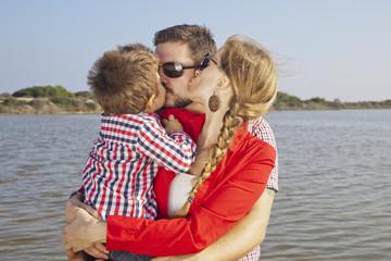 Mamá e hijo dando un beso a papá