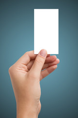 hand holding a white business card on a blue background