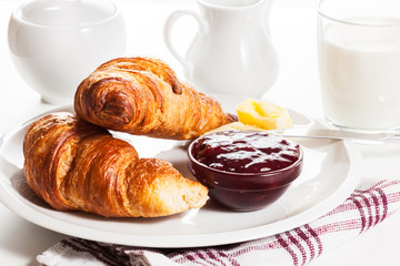 Fresh croissants with butter and a glass of milk