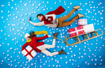 Young couple on sledge with Christmas presents