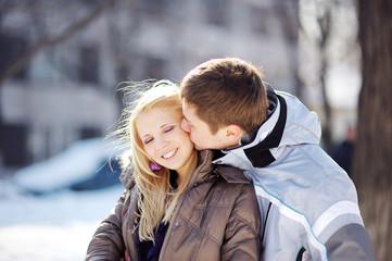 boy kissing a girl in winter