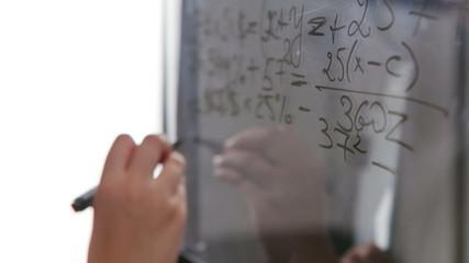 Young beautiful woman at the blackboard writing formulas