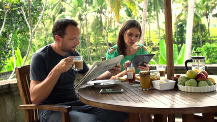 Couple, reading newspaper, drinking coffee and using tablet comp