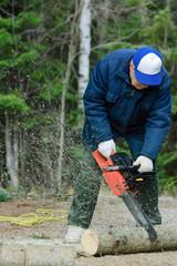 Active senior cutting a fallen tree