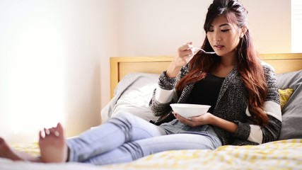 asian teen girl eating chicken soup on bed