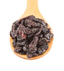 Black raisin on wooden spoon over white background