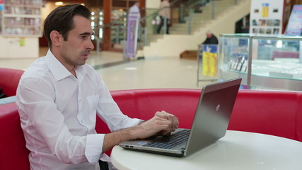 Man in despair and hesitant at work with a laptop