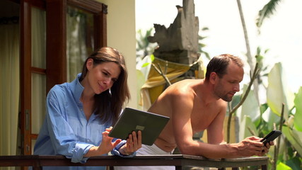 Young couple using tablet computer on terrace