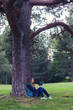 Teenage girl sitting under the tree and reading book