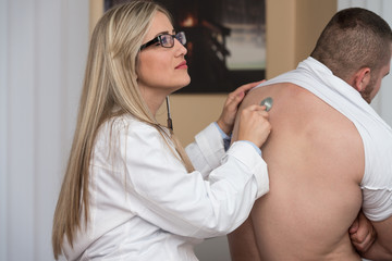 Listening Back Of Patient With Stethoscope
