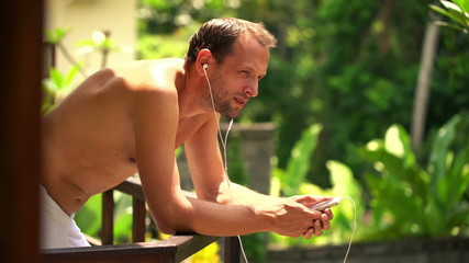 Man listening to music on cellphone, singing sad song in towel o