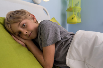 Ill child lying in hospital bed