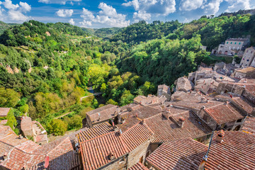 View of a green valley in Sorano over red roofs, Italy