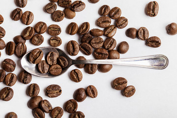 Teaspoon and coffee beans on white