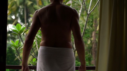 Man in towel unveil curtains and walking out on terrace