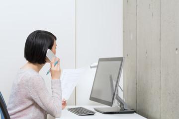 電話しながら仕事をする女性