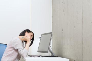 パソコン画面を見て悩む女性