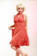 Beautiful pinup girl in blond wig and retro red dress