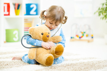 Cute little girl playing doctor with plush toy at home
