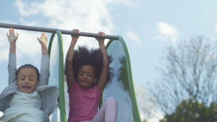 Two young children playing on a slide in a playground