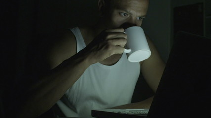 Man on his laptop at night pleased with his work