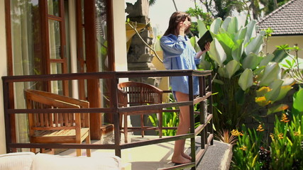 Pretty woman in men shirt using tablet computer on terrace