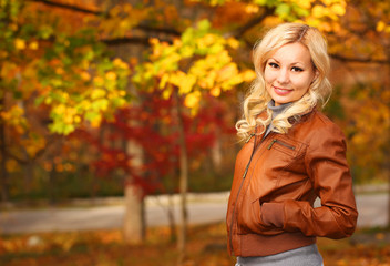 Autumn Woman. Fall. Blonde Girl with Yellow Leaves
