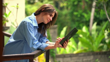 Beautiful woman in men shirt using tablet computer on terrace