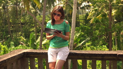 Young, pretty woman using tablet computer on terrace