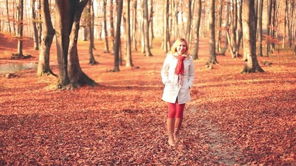 Blonde woman walking through a forest during autumn