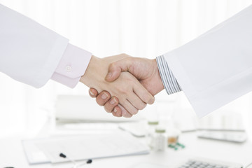 Handshake of female doctors and male doctor