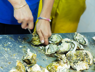 worker opening oysters