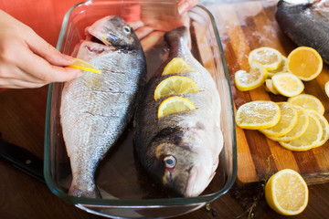 housewife putting pieces of lemon in fish