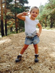 Young girl doing the victory sign in the mountains