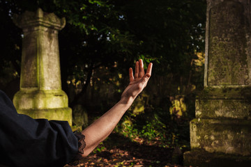Raised hand by grave