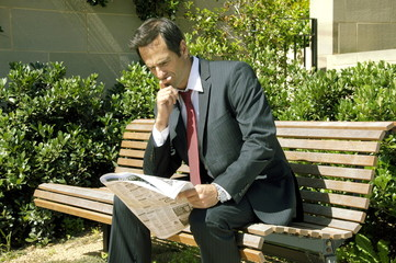 Mann im Anzug liest Zeitung