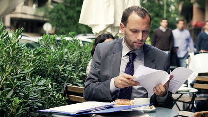 Young businessman comparing, checking documents sitting in cafe