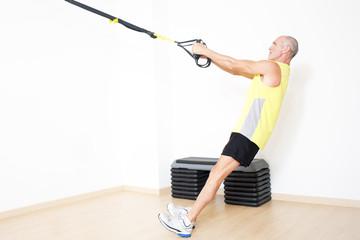 Older man making suspension training