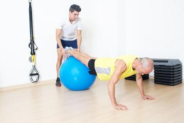 Senior beim Suspension Training mit Trainer