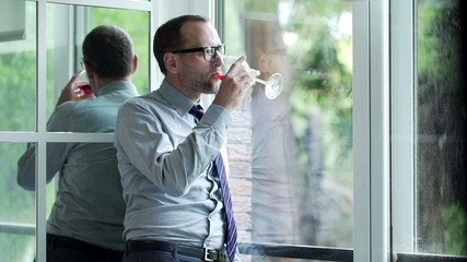 Attractive businessman drinking red wine standing by the window