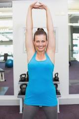 Fit brunette warming up in fitness studio