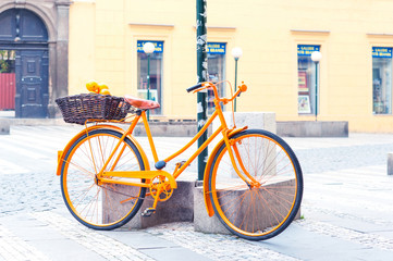 Orange provence rural bicycle with fruits in wicker basket.