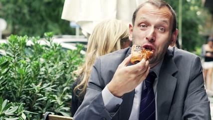Portrait of happy businessman eating sweet bun sitting in cafe