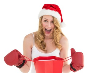 Shocked blonde opening a shopping bag with boxing gloves