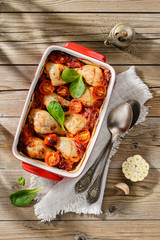 Baked chicken sticks in tomato sauce with onion, pepper and garl