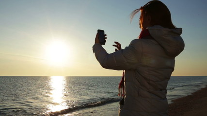 woman shooting on smartphone at sea beach