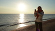 woman shooting on smartphone at sea beach